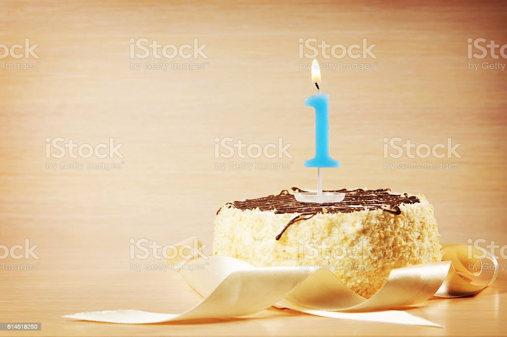 Birthday cake with burning candle as a number one stock photo