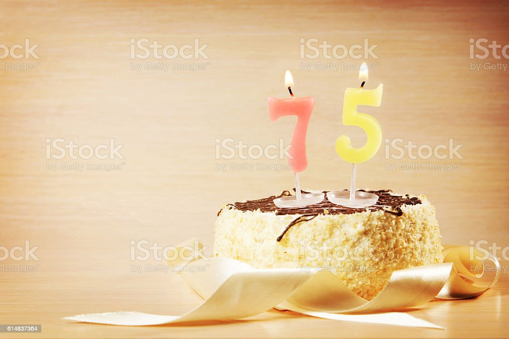 Birthday cake with burning candle as a number seventy five stock photo