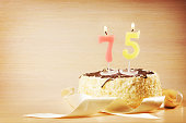 Birthday cake with burning candle as a number seventy five
