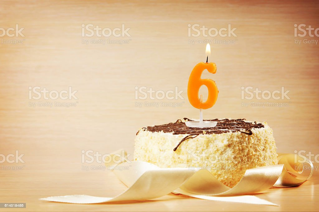 Birthday cake with burning candle as a number six stock photo