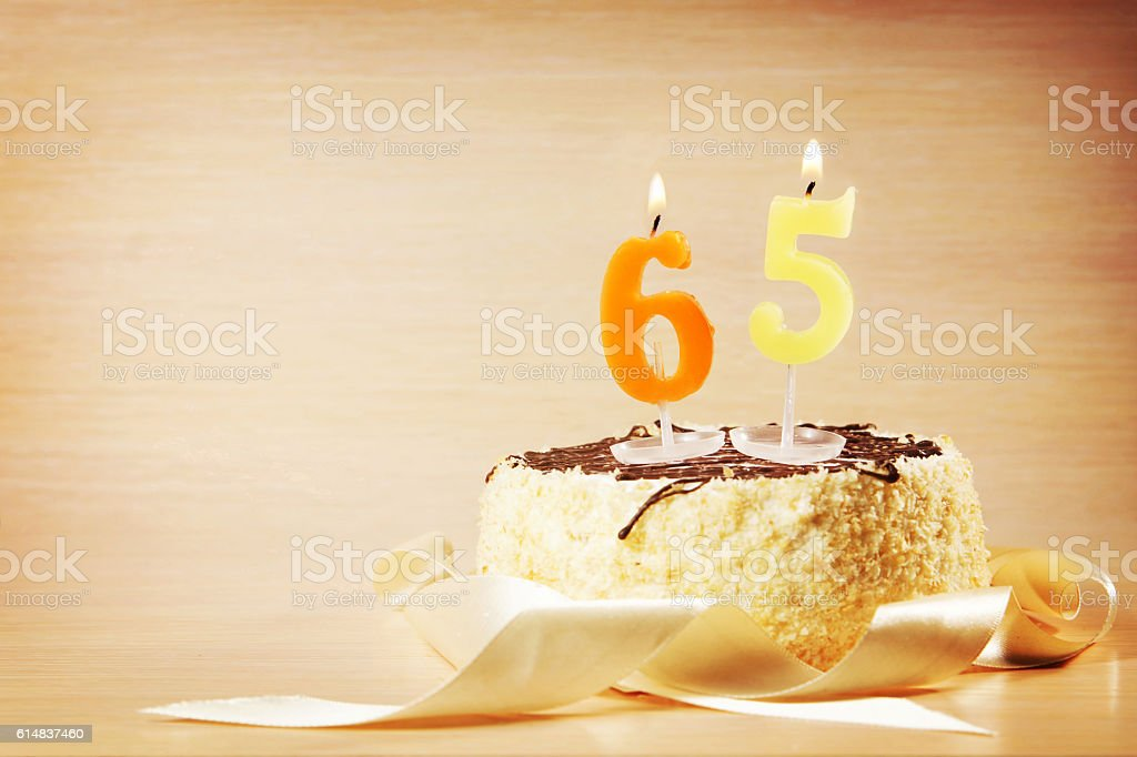 Birthday cake with burning candle as a number sixty five stock photo