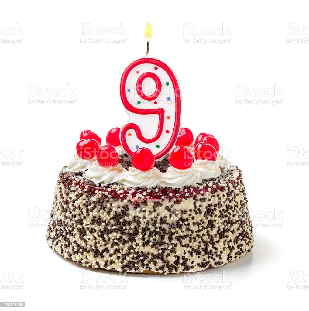 Birthday cake with burning candle number 9 stock photo