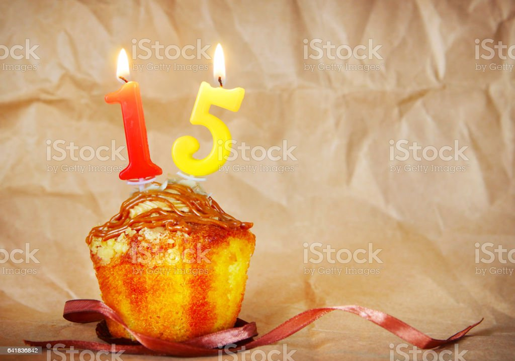 Birthday cake with burning candles as number fifteen stock photo