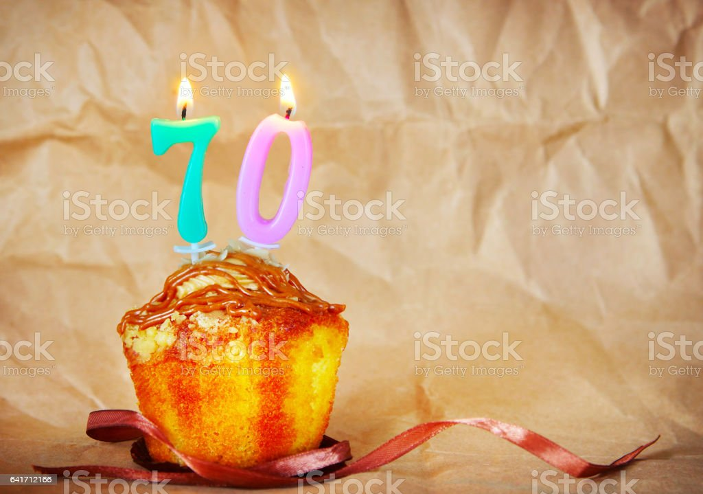Birthday cake with burning candles as number seventy stock photo