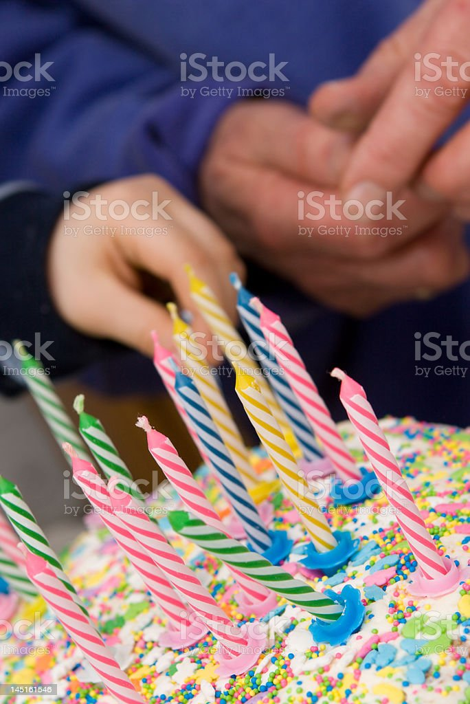 birthday cake with candles - hands in background royalty-free stock photo