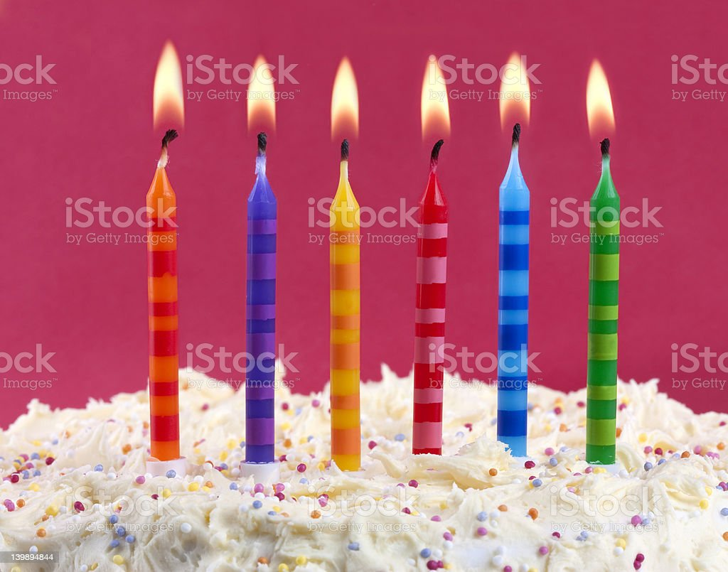 Birthday cake with sprinkles and six colorful lit candles stock photo