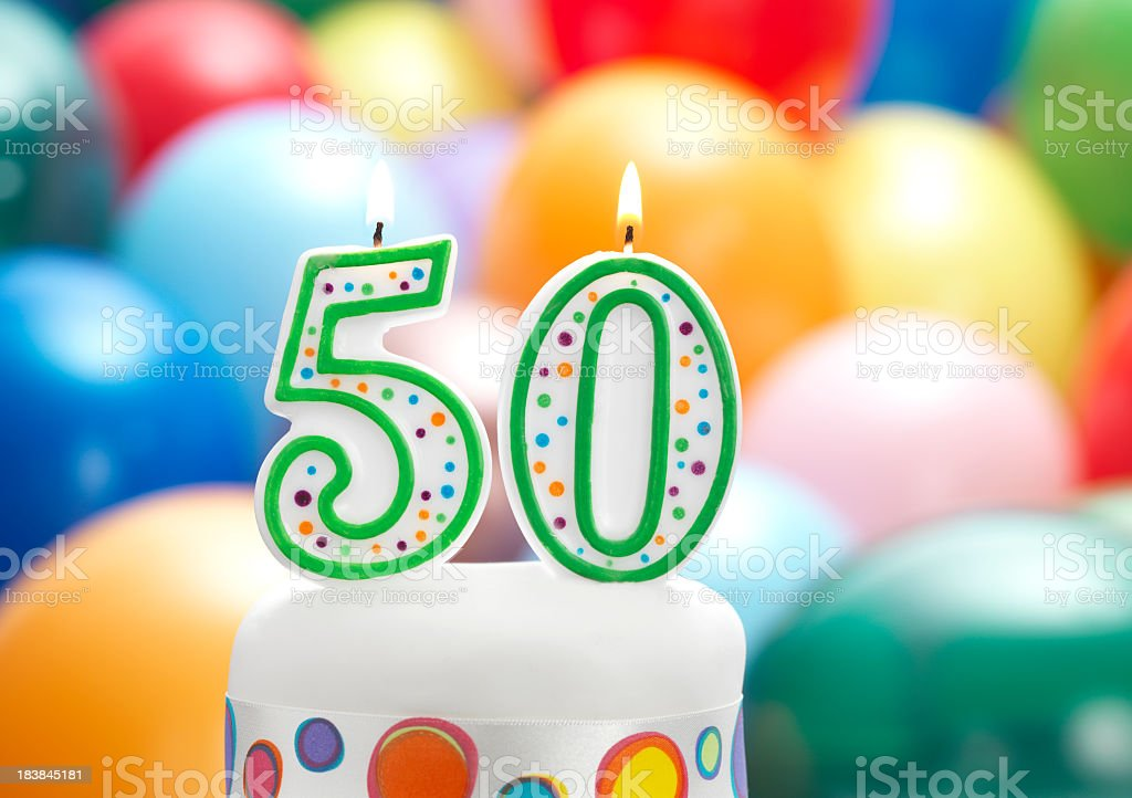Birthday candles that say 50 with blurred balloons in back stock photo
