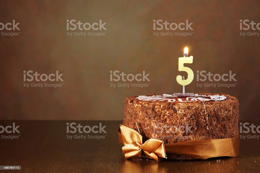 Birthday chocolate cake with burning candle as a number five stock photo