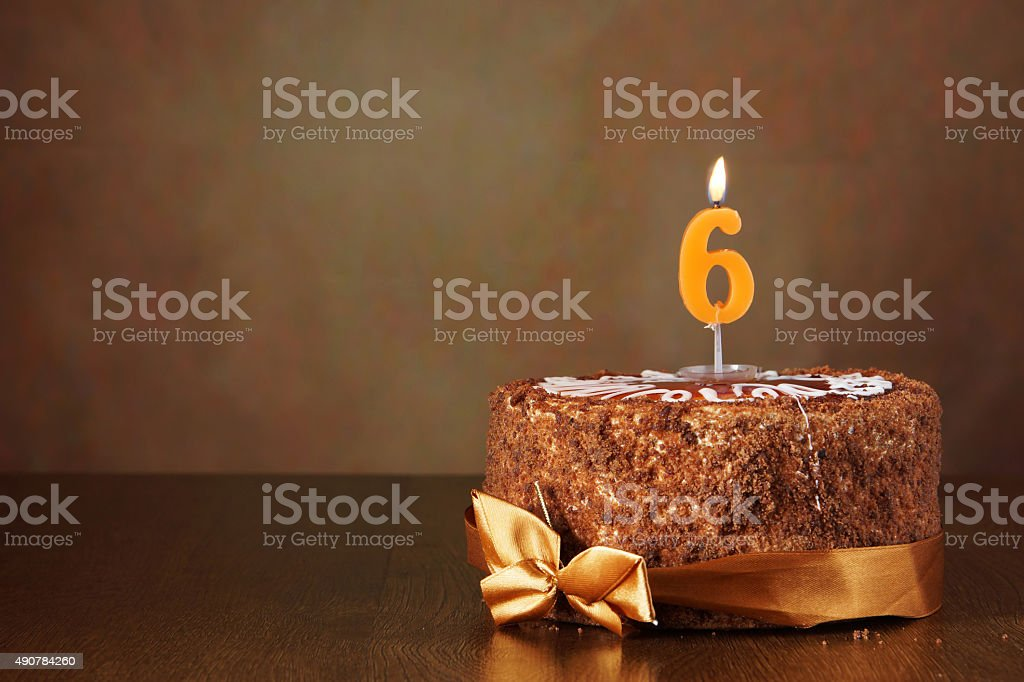 Birthday chocolate cake with burning candle as a number six stock photo