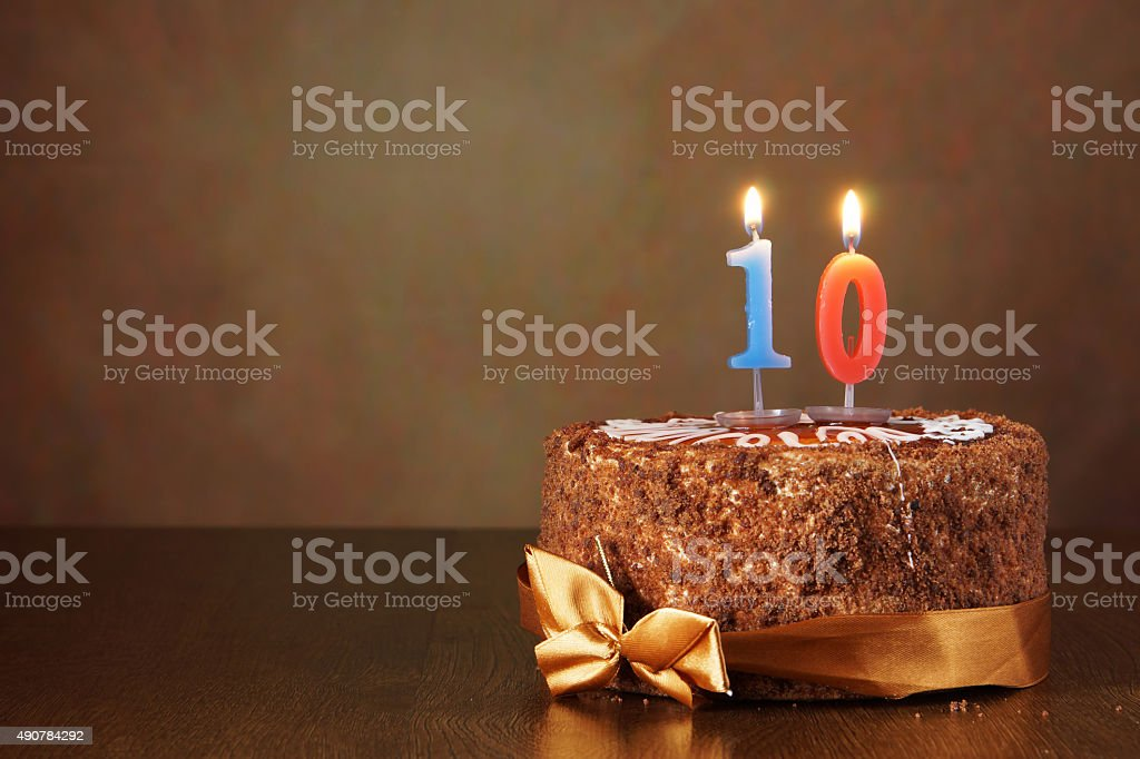 Birthday chocolate cake with burning candle as a number ten stock photo