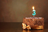 Birthday chocolate cake with burning candle as a number three
