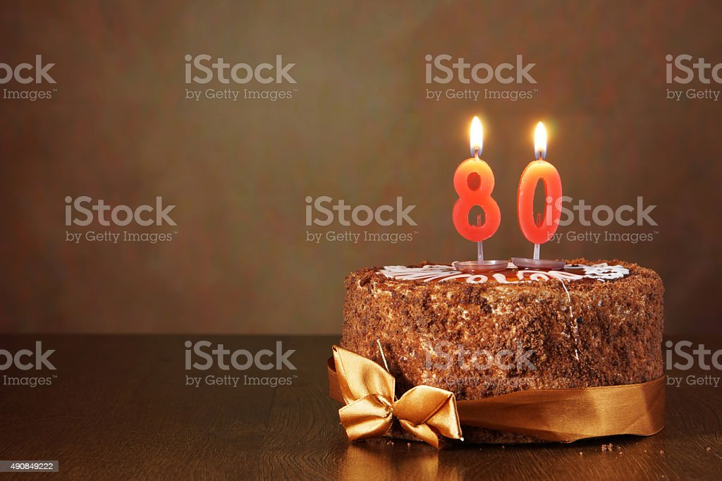 Birthday chocolate cake with burning candles as a number eighty stock photo