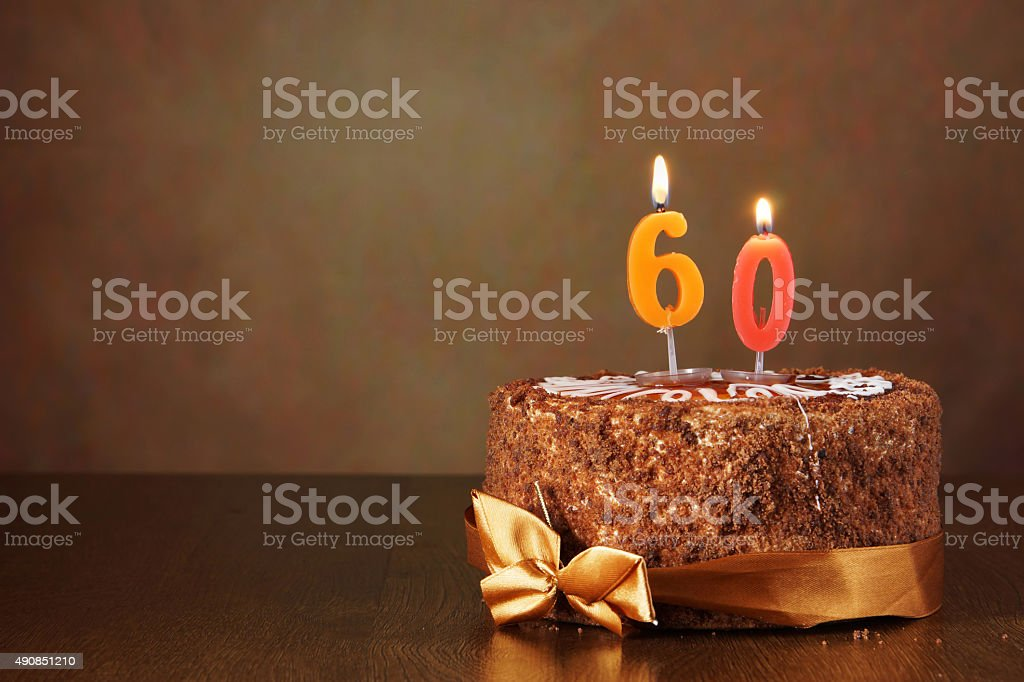Birthday chocolate cake with burning candles as a number sixty stock photo