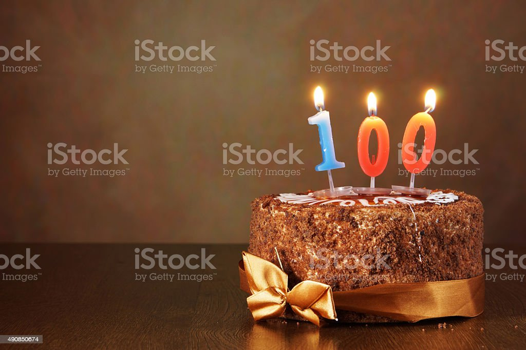 Birthday chocolate cake with burning candles as number one hundred stock photo