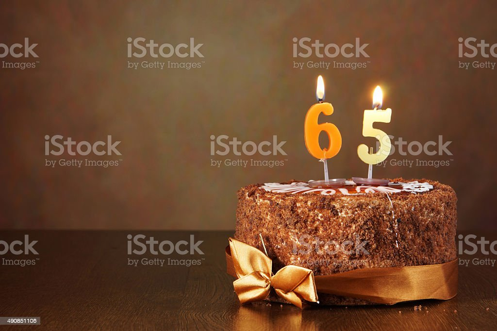 Birthday chocolate cake with burning candles as number sixty five stock photo