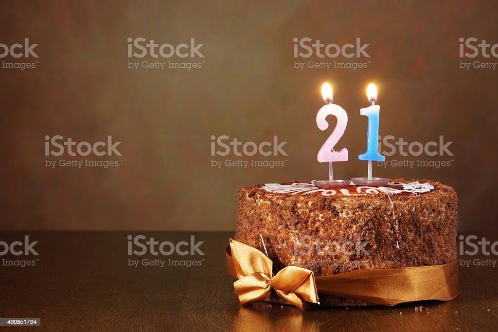 Birthday chocolate cake with burning candles as number twenty one stock photo