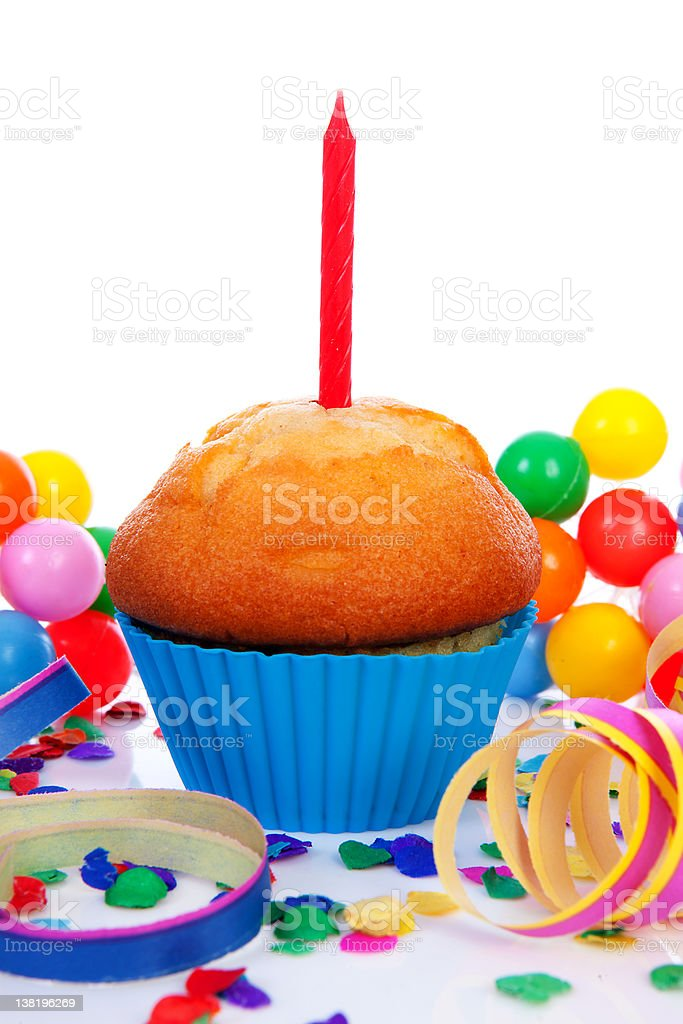 Birthday cupcake with candle streamers and colorful confetti stock photo