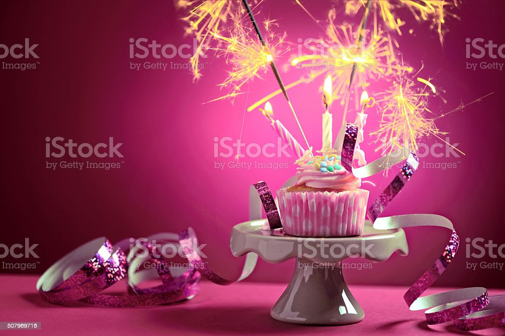 Birthday cupcake with candles and sparklers stock photo