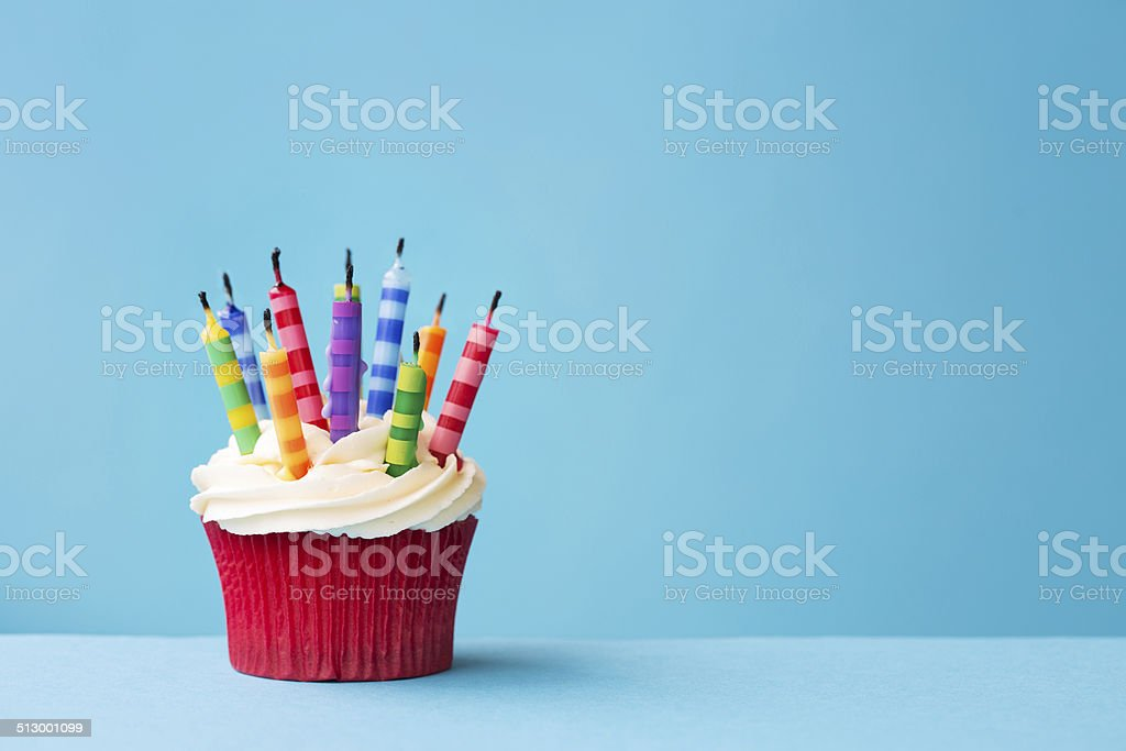 Birthday cupcake with candles blown out stock photo
