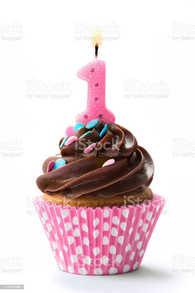 A birthday cupcake with the number one and chocolate icing stock photo