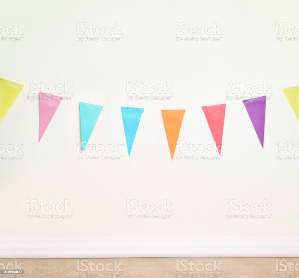 Birthday decoration flags on a plain white wall stock photo