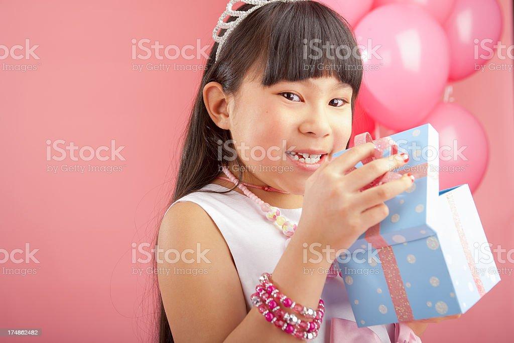 Birthday girl opening her gift royalty-free stock photo