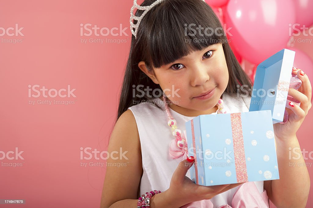 Birthday girl opening her gift royalty-free stock photo