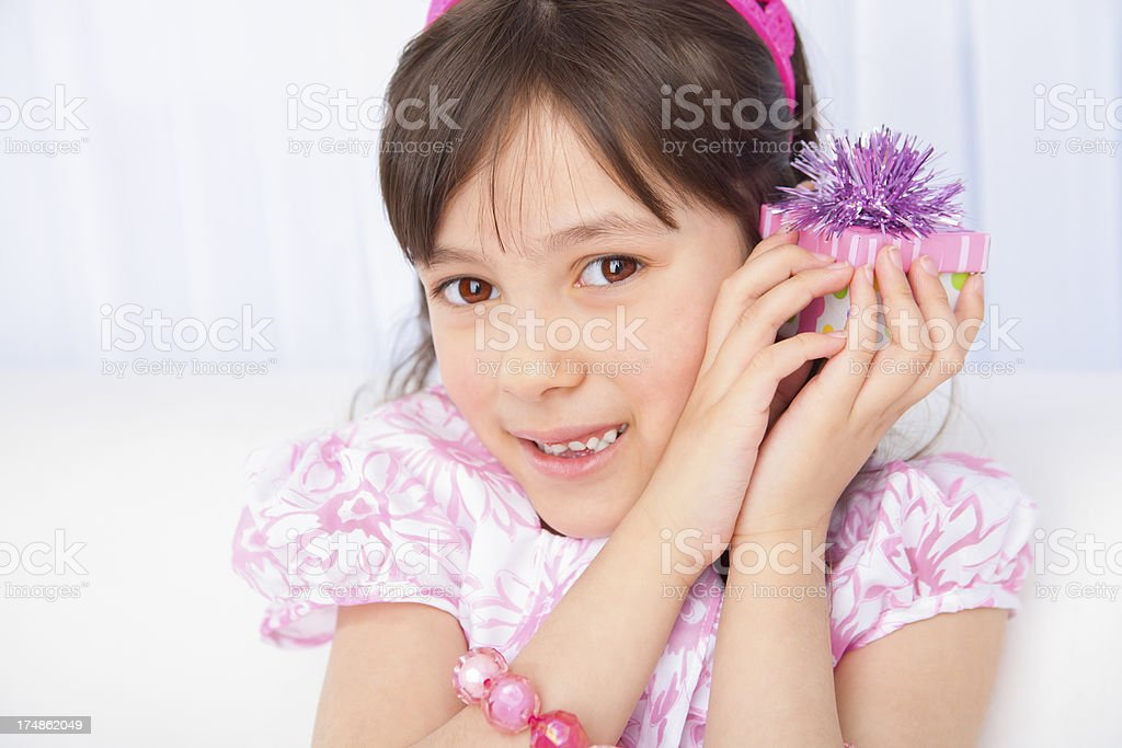Birthday girl trying to figure out her present royalty-free stock photo