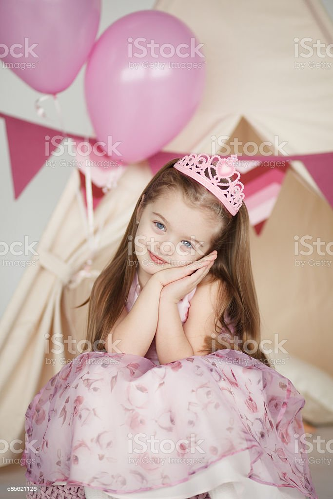 Birthday girl wearing a pink dress and crown stock photo