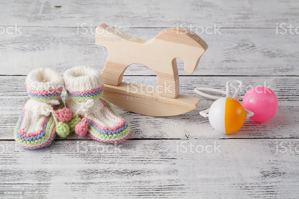 Birthday invitation. Rattle, wood horse  and knitted booties for stock photo