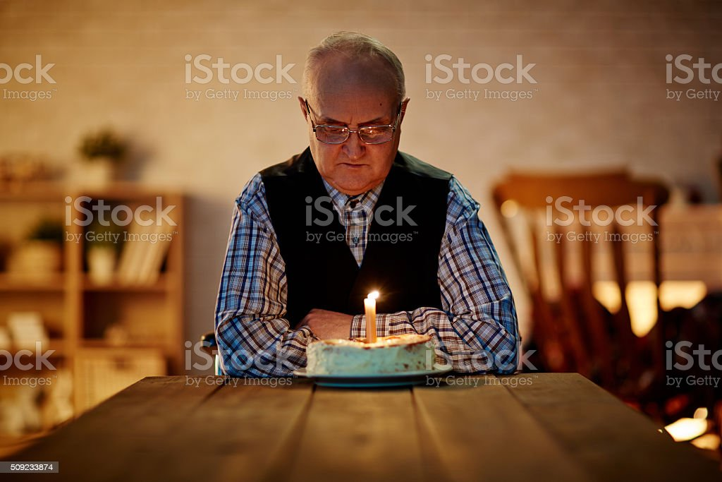 Mature man looking at birthday cake with one candle