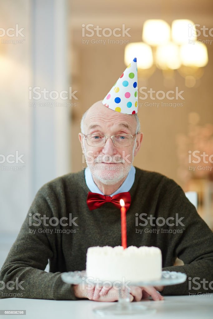 Aged man in birthday cap sitting by table in front of cake with...
