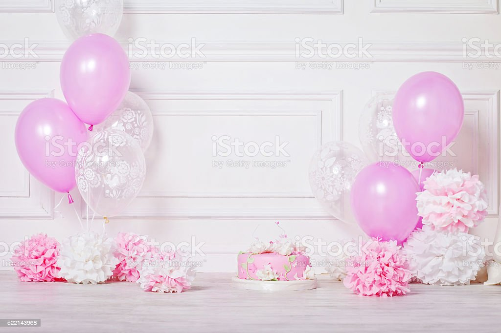 Birthday or wedding cake, pompons and balloons. White and pink. stock photo