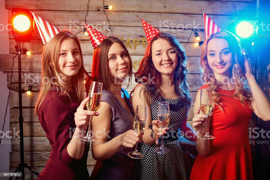 Birthday party girlfriends. Beautiful girl in a cap with glasses stock photo
