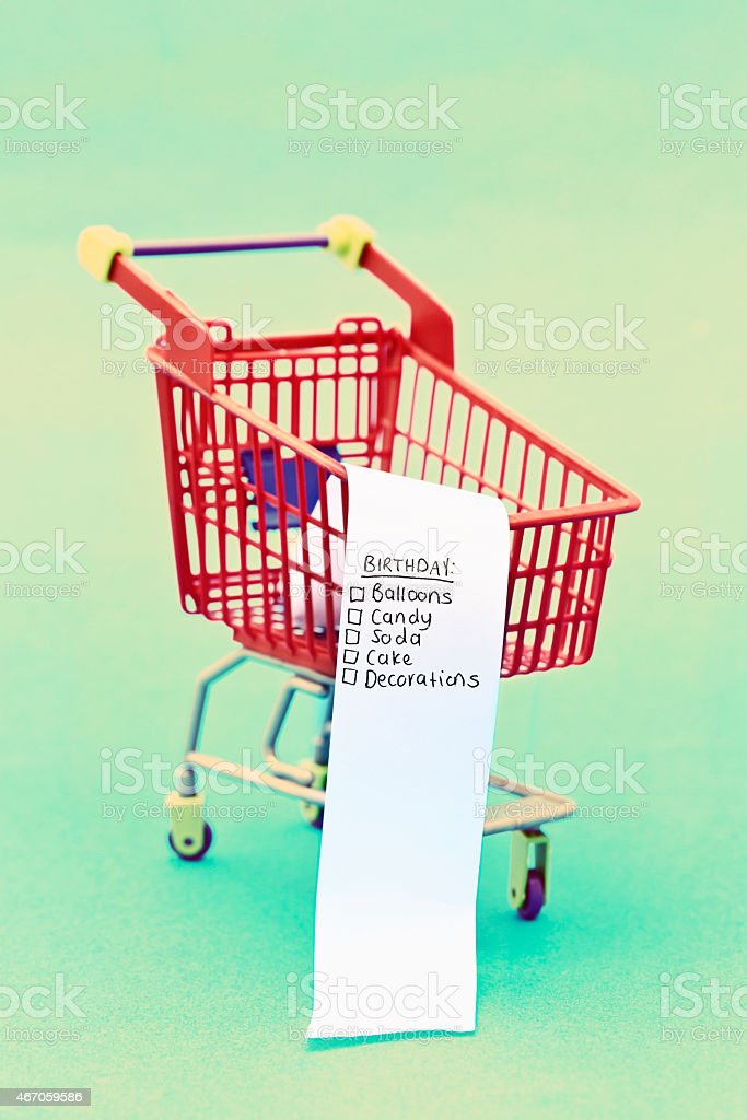 Birthday party shopping list in tiny trolley stock photo