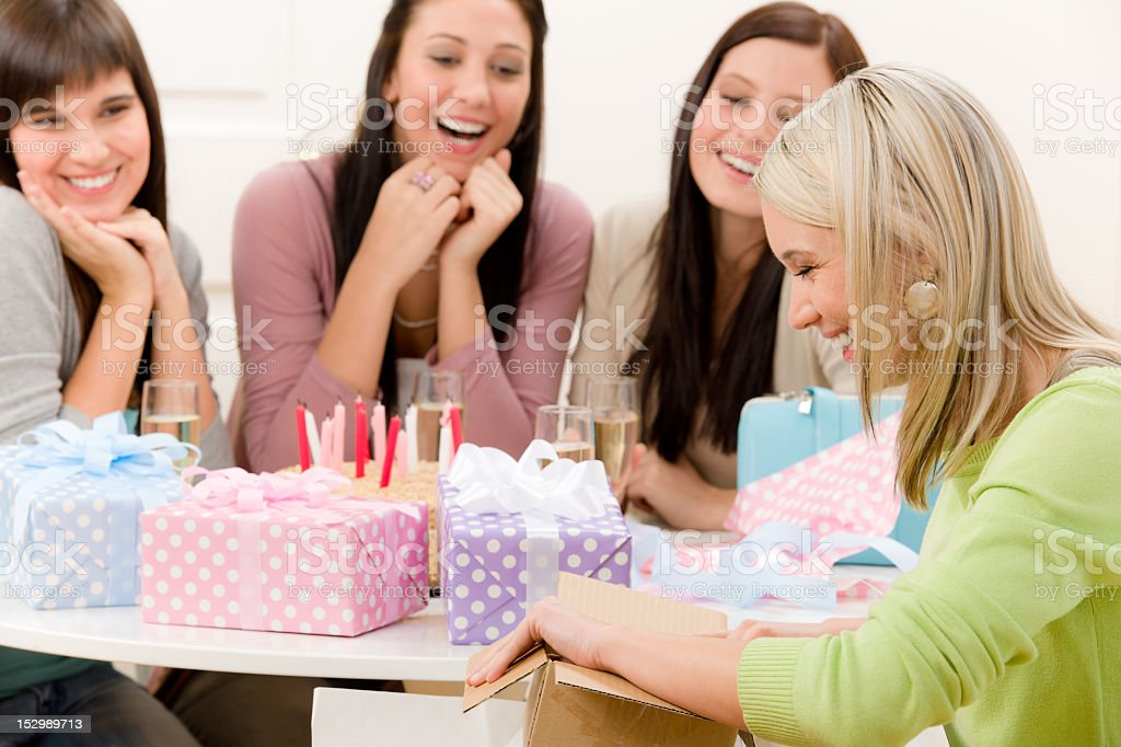 Birthday party - woman unwrap present, celebrating royalty-free stock photo