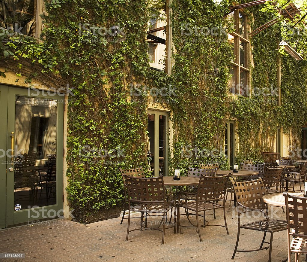 Bistro outdoors. Sidewalk cafe. Ivy growing on walls. Patio tables. stock photo