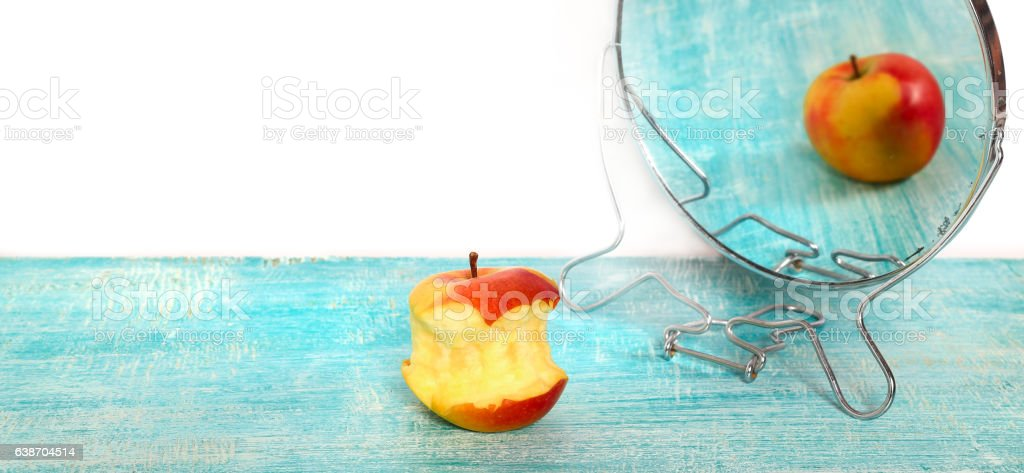 Bit of apple and reflection of the whole apple stock photo