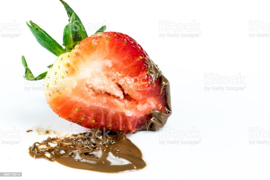 Bite of juicy strawberry covered in chocolate stock photo