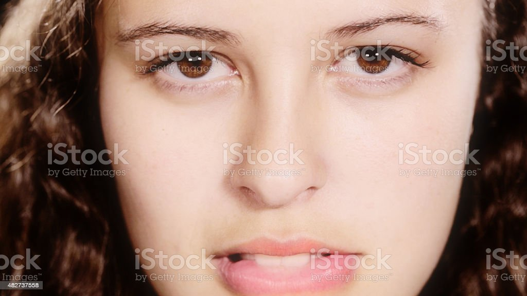 Biting her lip, beautiful young woman looks embarrassed and flirtatious stock photo