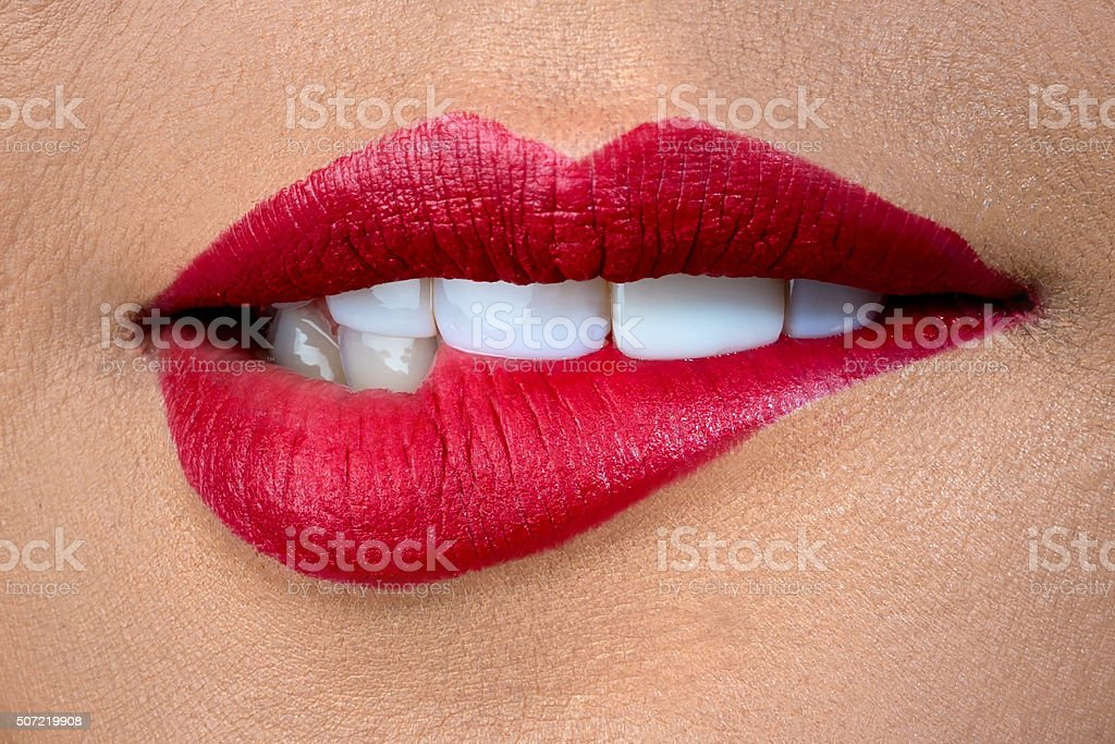 Biting red lips stock photo