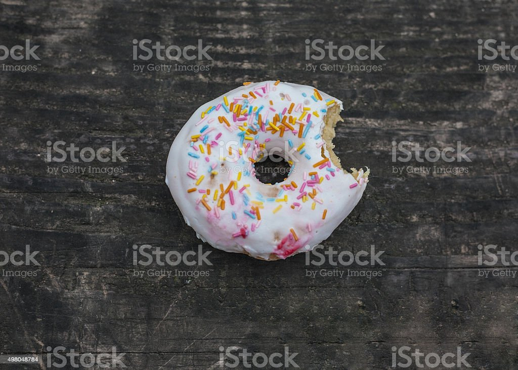 Bitten doughnut on a wooden table royalty-free stock photo