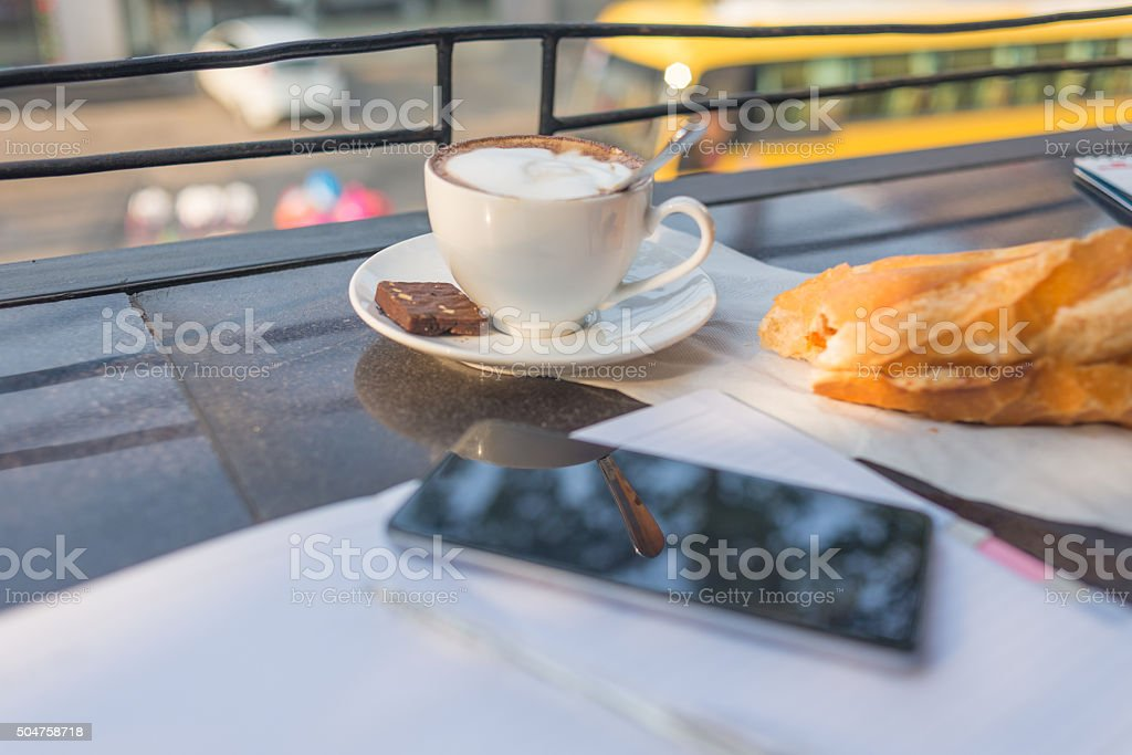 Bitten out bread, cup of cappuccino and smartphone on desk stock photo