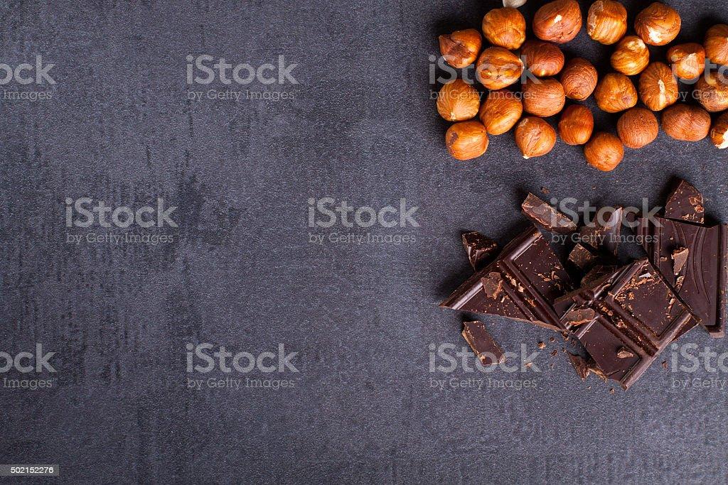 Bitter chocolate and hazelnuts on corner, black stone background. stock photo