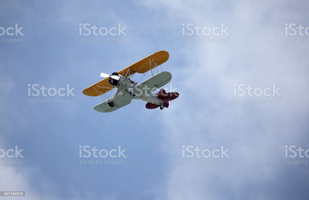 Bi-wing, propeller driven airplane and clouds.  Copy space. stock photo