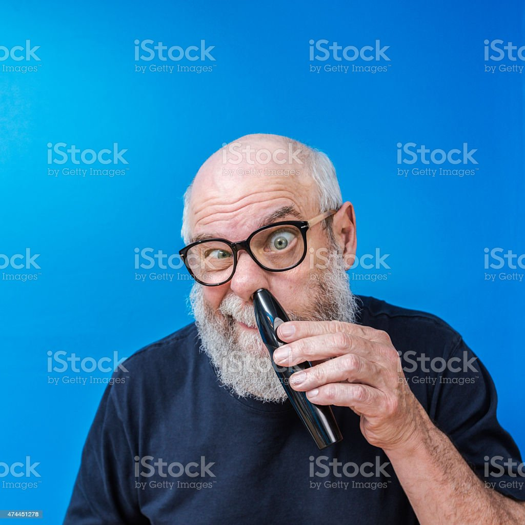 Bizarre Senior Man Clipping Nose Hair With Electric Razor stock photo