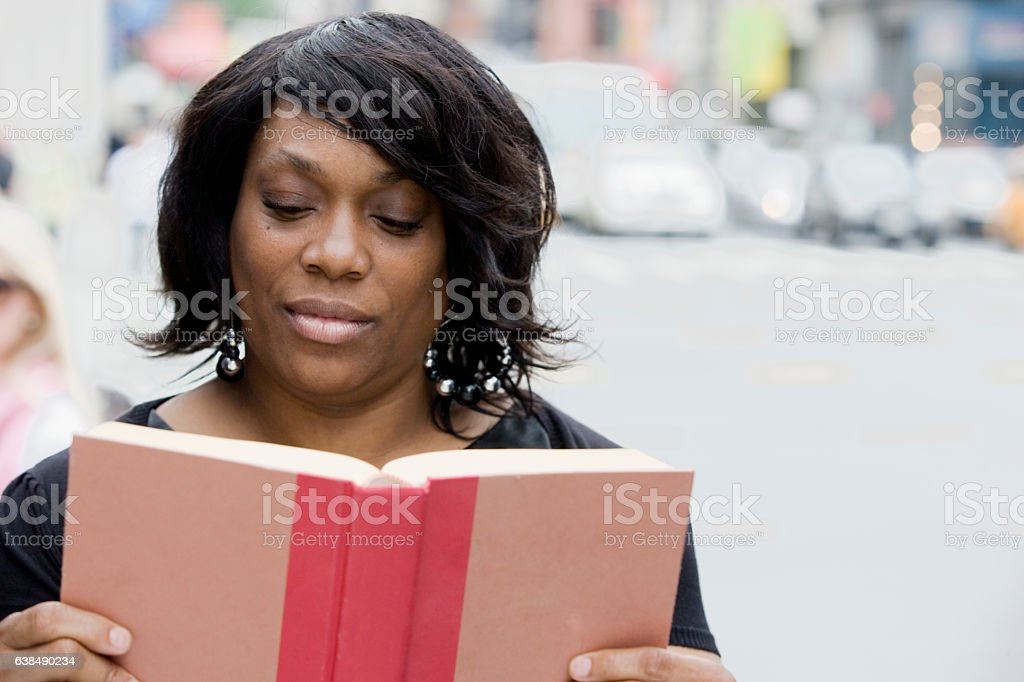 Black adult woman reading story book in downtown city stock photo