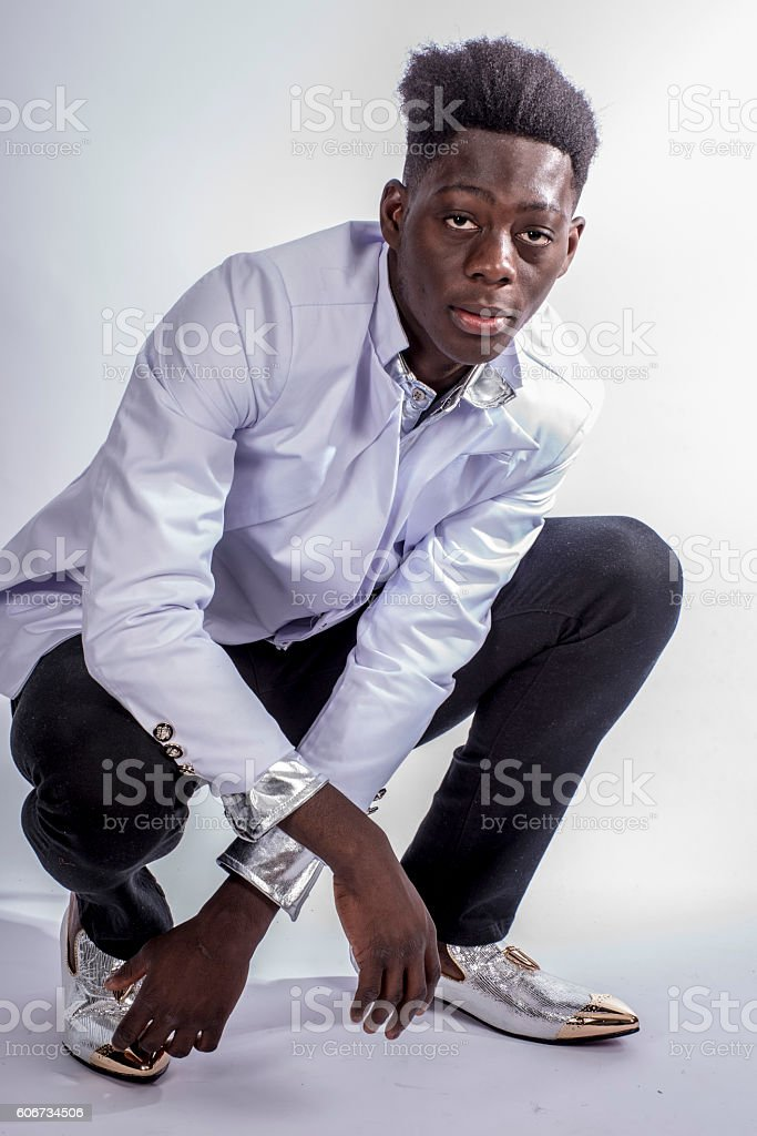 Black African man makes a dance move close to floor. stock photo