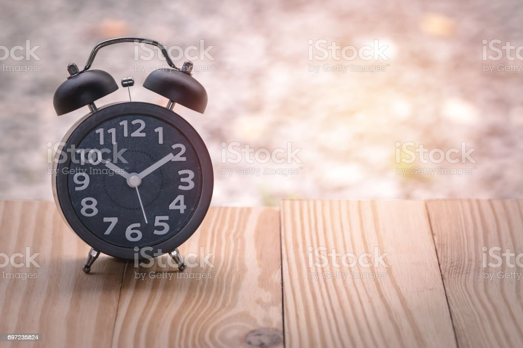 Black alarm clock on wood table in burred background stock photo