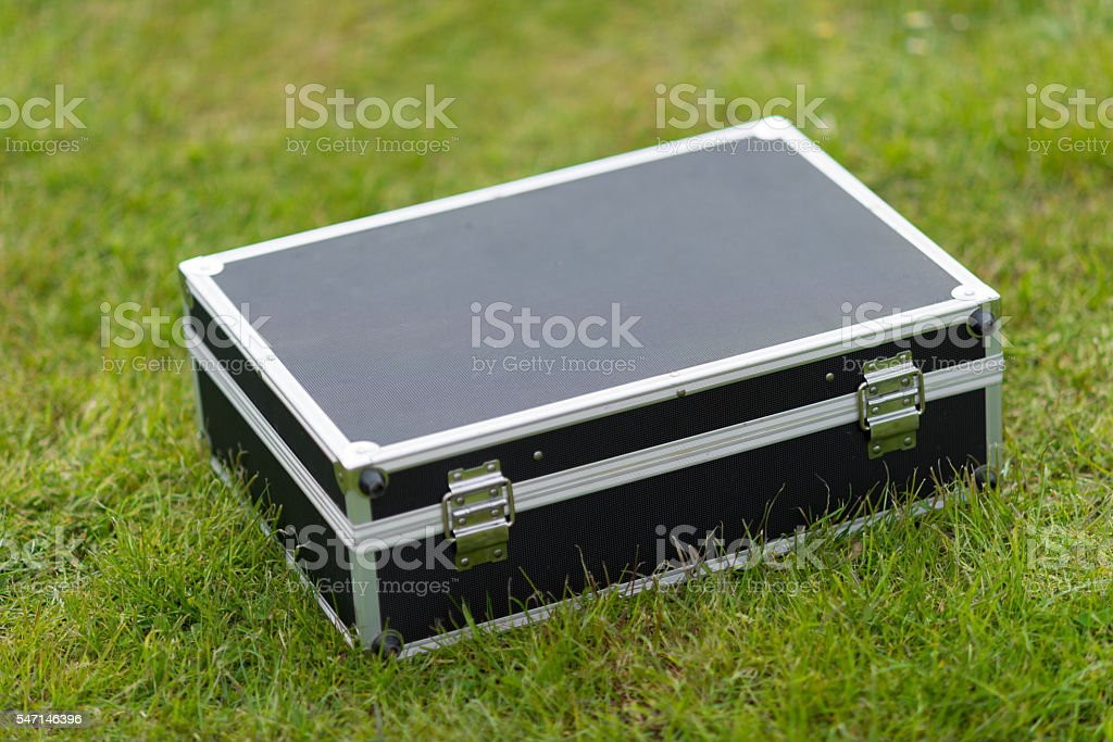 black aluminium suitcase on meadow stock photo